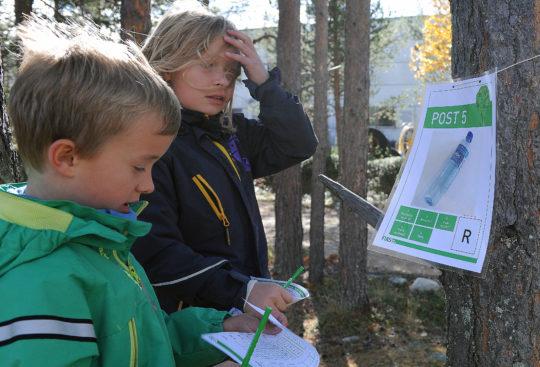 Bildet viser to skolebarn som deltar på natursti om kildesortering