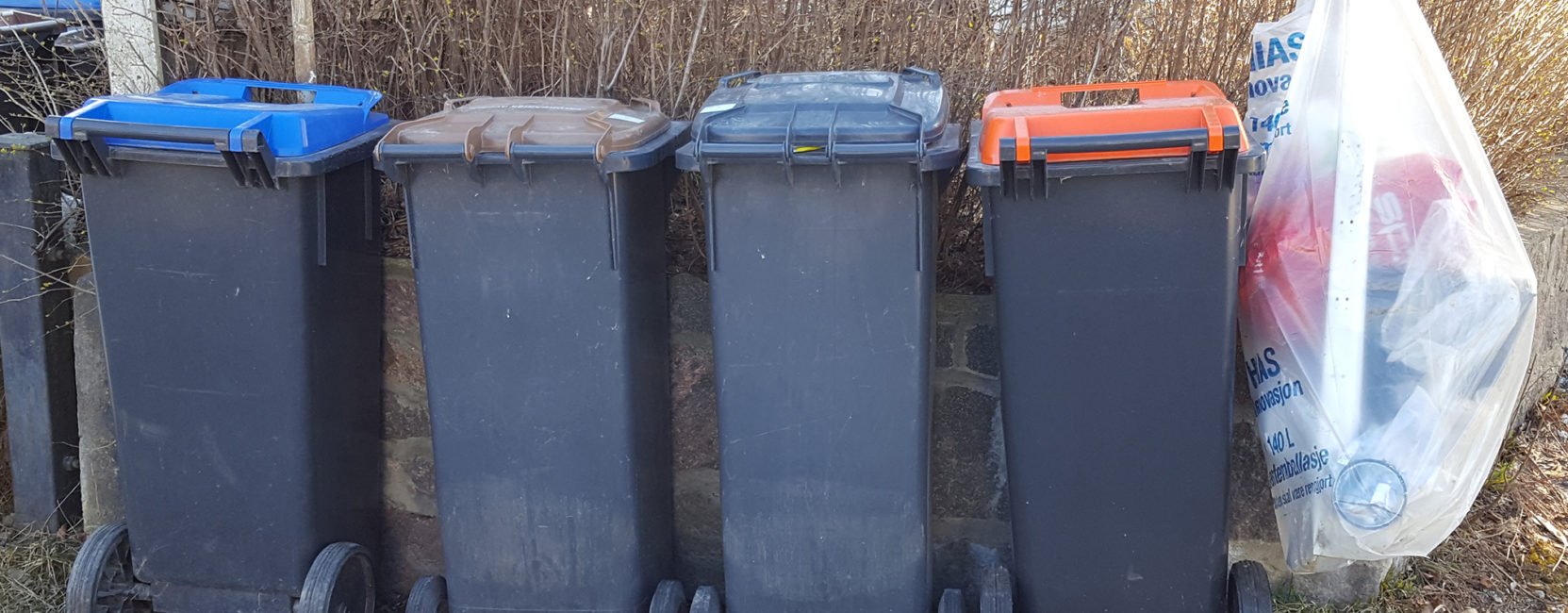 Fire søppeldunker med forskjellig farge på lokket, og en plastsekk.